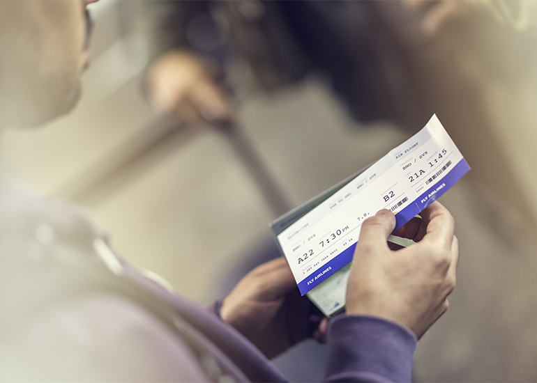 Close up of a man holding airplane ticket